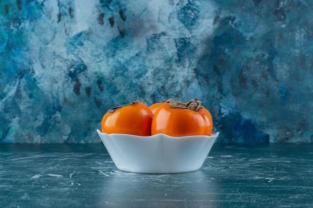 Een kom met persimmonvruchten, op de marmeren tafel.