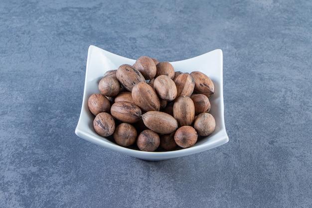 Een kom met rauwe noten op het marmeren oppervlak