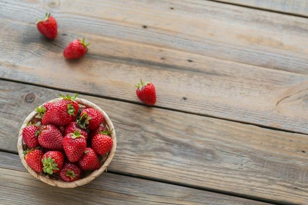 Een kom met rode sappige aardbeien op rustieke houten tafel
