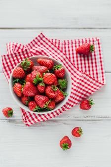 Een kom met rode sappige aardbeien op witte houten tafel. gezond en dieet snack food concept. Premium Foto