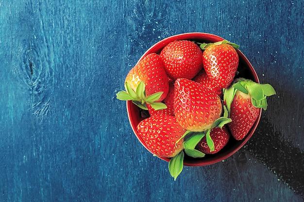 Een kom met sappige aardbeien op een donkerblauwe achtergrond met kopie ruimte.