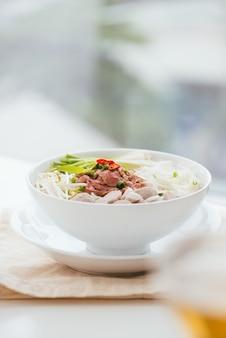 Een kom met traditionele vietnamese pho-noedels