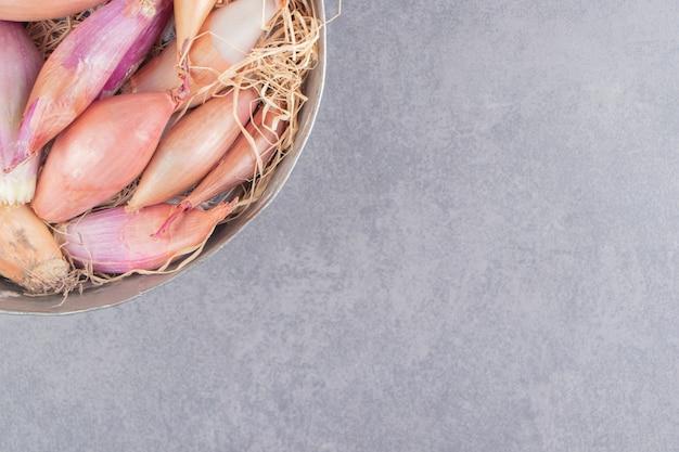 Een kom met uien op het marmeren oppervlak