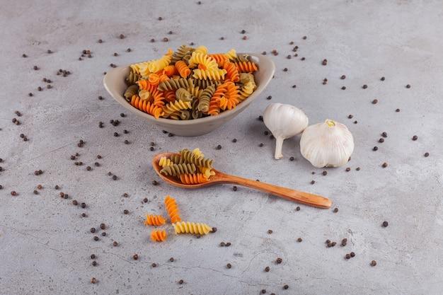 Een kom met veelkleurige rauwe spiraalvormige pasta met knoflook en peperkorrels.
