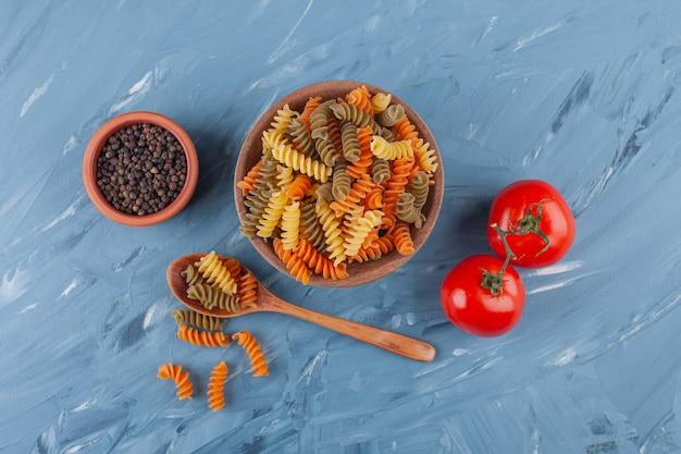 Een kom met veelkleurige rauwe spiraalvormige pasta met verse rode tomaten en kruiden.
