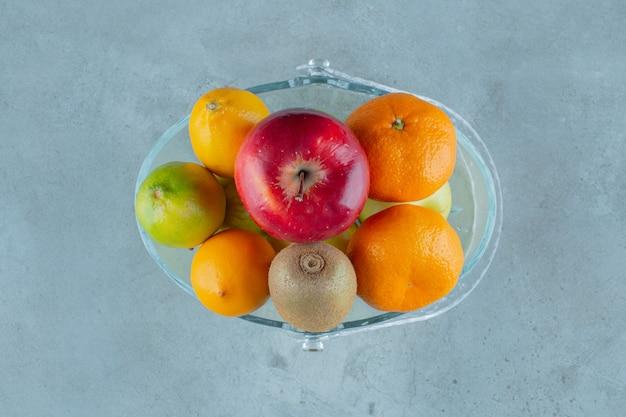 Een kom met verschillende soorten fruit, op de marmeren achtergrond. hoge kwaliteit foto