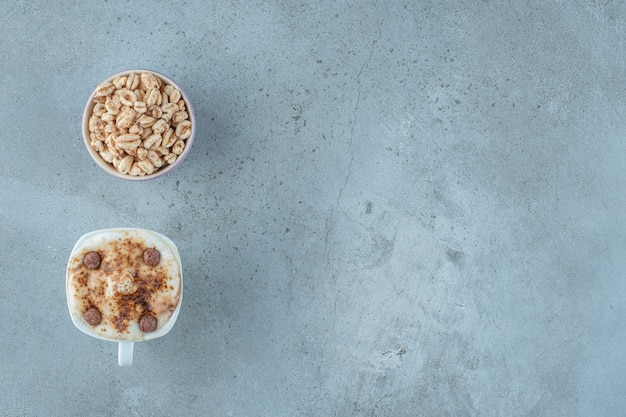 Een kom muesli en een kopje cappuccino, op de blauwe achtergrond.