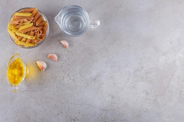 Een kom multi gekleurde rauwe pasta met knoflook en olie op een stenen tafel.