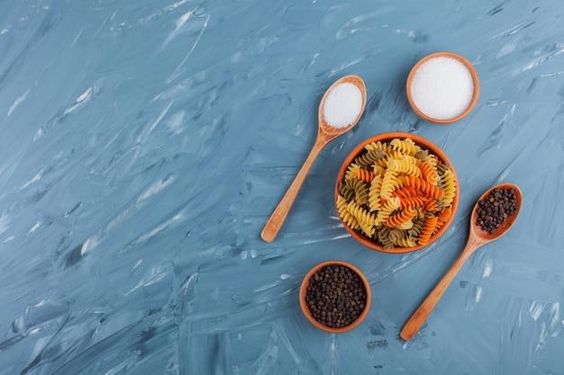 Een kom multi gekleurde ruwe spiraalvormige deegwaren met zout en peperkorrels.