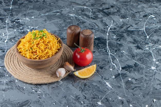 Een kom noedels op een onderzetter naast tomaten, citroen en knoflook, op de marmeren achtergrond.