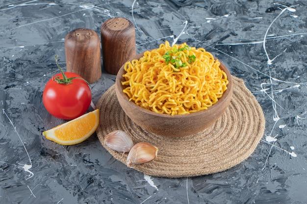 Een kom noedels op een onderzetter naast tomaten, citroen en knoflook, op het marmeren oppervlak.
