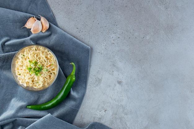 Een kom noedels, peper en knoflook op een stuk stof, op de marmeren achtergrond.