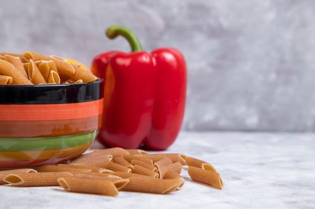 Een kom ongekookte buisdeegwaren met rode paprika