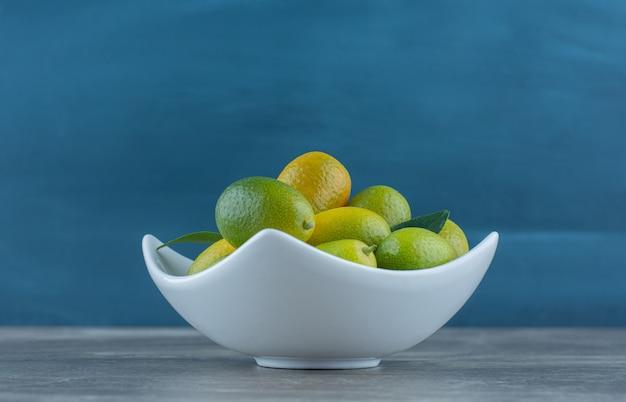 Een kom onrijpe kumquat, op de marmeren tafel.