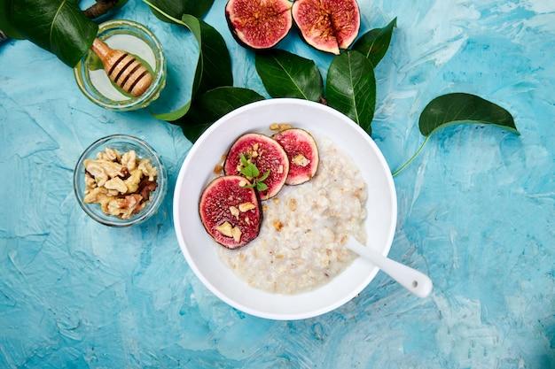 Een kom pap met vijgen segmenten en walnoten op blauwe achtergrond. plat liggen. kopieer ruimte. bovenaanzicht. gezond ontbijt.