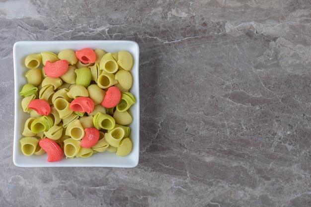 Een kom pasta klaar om te koken, op de marmeren achtergrond.