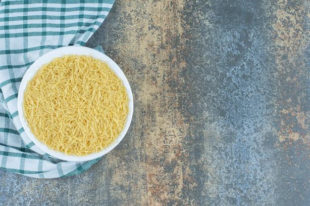 Een kom pasta op de handdoek, op de marmeren achtergrond.