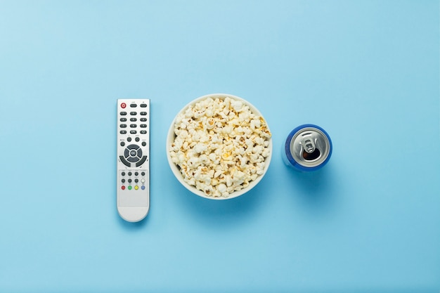 Een kom popcorn, een afstandsbediening van een tv, een blikje met een drankje op een blauwe achtergrond. het concept van tv kijken, film, tv-series, sport, shows. plat lag, bovenaanzicht.