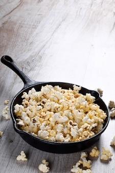 Een kom popcorn op een houten tafel