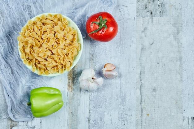 Een kom rauwe pasta met tomaat, peper en knoflook.