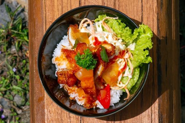 Een kom rijst met chiken katsu en groenten, op teakhouten tafel, japans restaurant in yogyakarta, indonesië