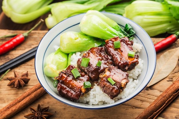 Een kom rijst met ribben in bruine saus