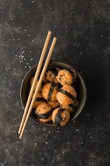 Een kom rijstballetjes met sesamzaadjes en nori zeewier, geserveerd met sojasaus, eetstokjes op een donkere achtergrond. bovenaanzicht met kopie ruimte