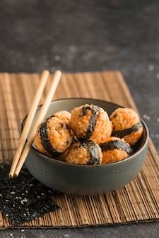 Een kom rijstballetjes met sesamzaadjes en nori zeewier, geserveerd met sojasaus, eetstokjes op een donkere achtergrond. zijaanzicht met een kopie ruimte. verticale oriëntatie