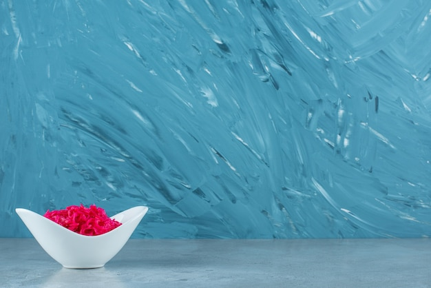 Een kom rode gefermenteerde zuurkool, op de blauwe tafel.