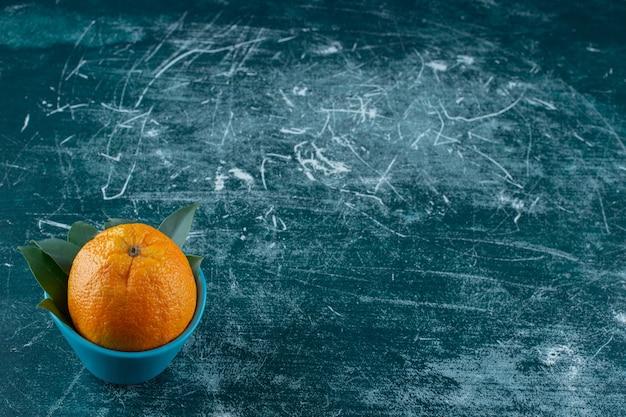 Een kom sinaasappel met bladeren, op de marmeren tafel.