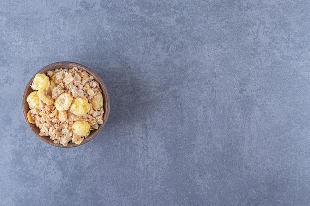 Een kom smaakvolle muesli, op de marmeren tafel.