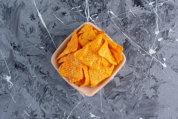 Een kom smakelijke chips, op het marmeren oppervlak