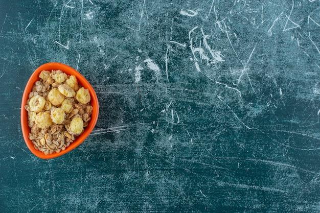 Een kom smakelijke granen op een, op de blauwe achtergrond. hoge kwaliteit foto