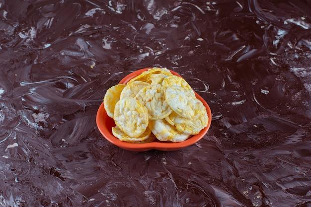 Een kom smakelijke kaaschips, op de marmeren tafel.