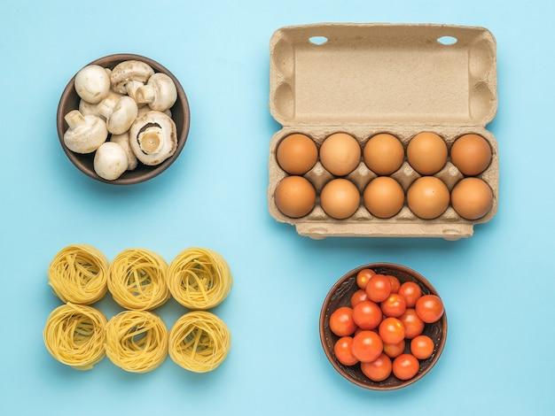 Een kom tomaten, een kom champignons, pasta en een doos eieren op een blauwe achtergrond. ingrediënten voor het maken van pasta.