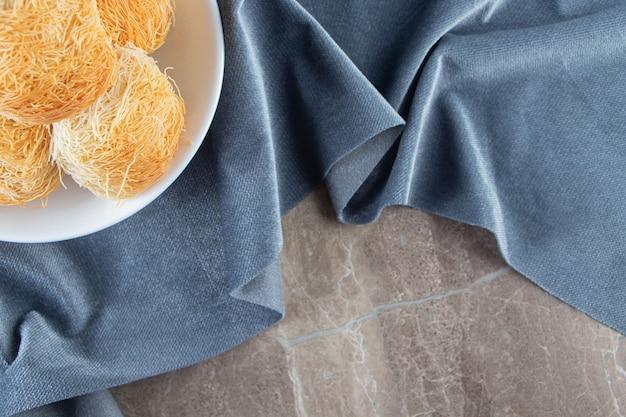 Een kom turkse dessertkadayif op stukjes stof op blauw.