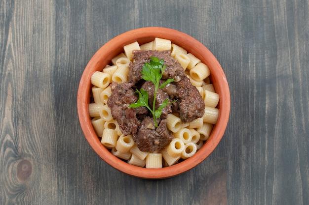 Een kom van klei met heerlijke macaroni en vlees
