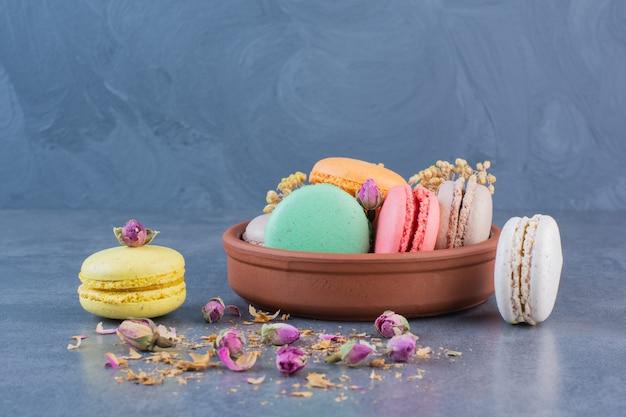 Een kom van klei vol macaroni koekjes van verschillende kleuren op een donkergrijs oppervlak