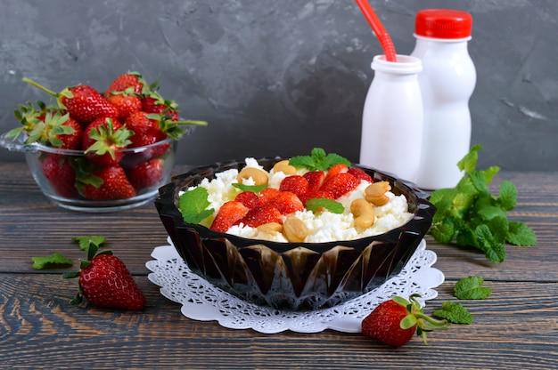 Een kom van verse zelfgemaakte kwark met aardbeien, munt en noten op een houten achtergrond. handig ontbijt. goede voeding.