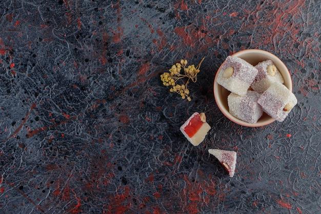 Een kom vol traditionele turkse lekkernijen met mimosa-bloem.
