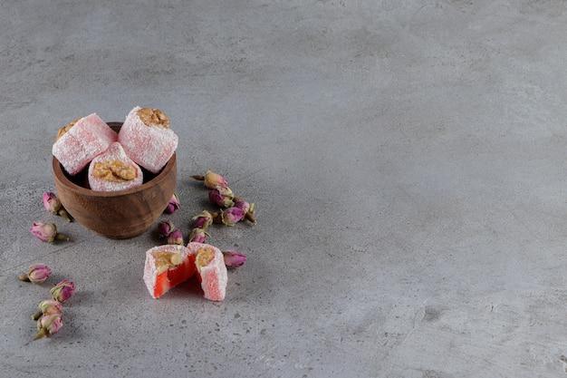 Een kom vol traditionele turkse lekkernijen met mimosa-bloem