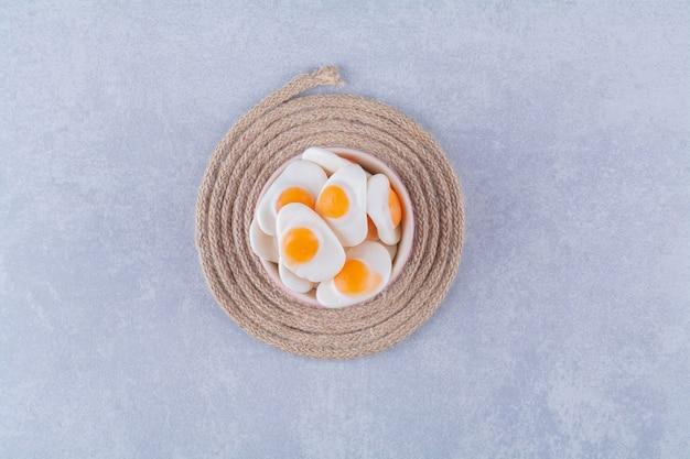 Een kom vol zoete gelei-gebakken eieren op een jute.