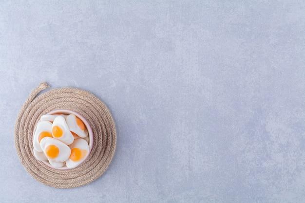 Een kom vol zoete gelei-gebakken eieren op een jute