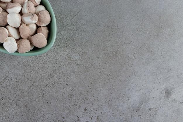 Een kom vol zoete ronde snoepjes op een stenen tafel.