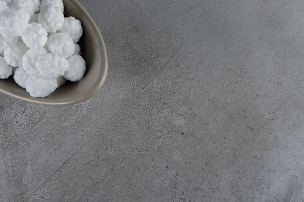 Een kom vol zoete witte snoepjes op een stenen tafel.