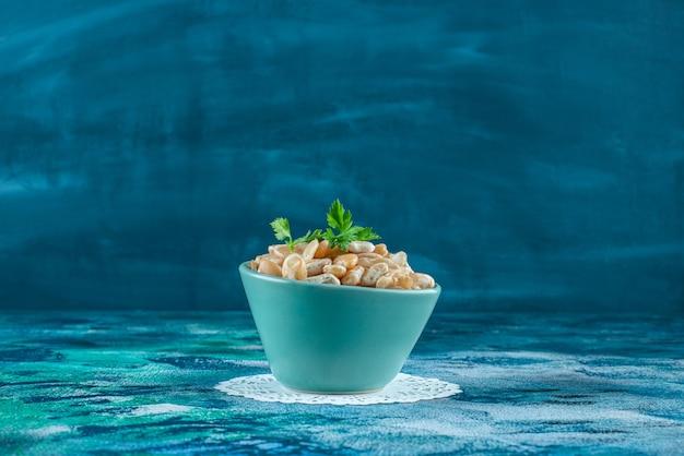 Een kom witte bonen met peterselie, op de blauwe achtergrond.