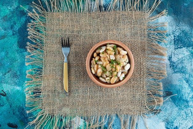 Een kom witte bonen naast de vork op een textuur, op de blauwe tafel.