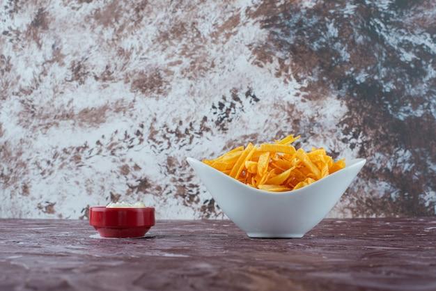 Een kom yoghurt en frietjes in een kom, op de marmeren tafel.
