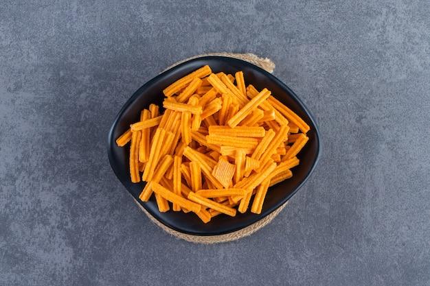Een kom zoete frietjes op onderzetter, op de marmeren achtergrond.