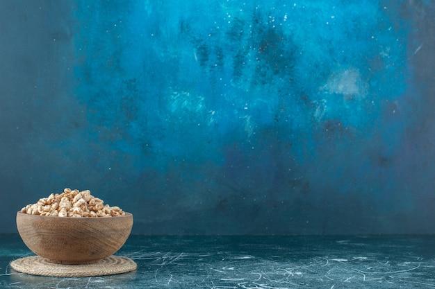 Een kom zoete muesli op een onderzetter, op de blauwe achtergrond. hoge kwaliteit foto